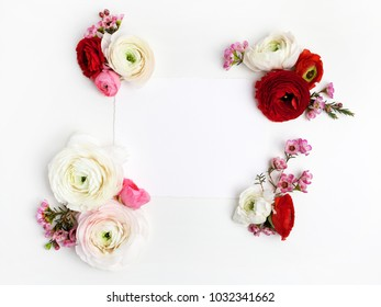 Frame with pink and red ranunculus, on white background. Flat lay, top view