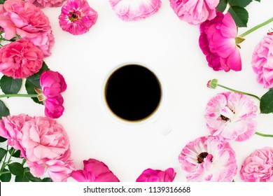 Frame of pink rose flowers and anemone with mug of black coffee on white background. Flat lay, Top view. Flowers texture.