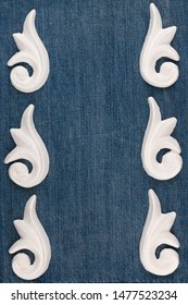 Frame of plaster decorative stucco molding on a denim background. Top view