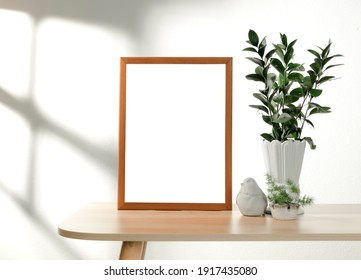 Frame or Poster mock up in living room and plants in vase with window shadow on white wall background.