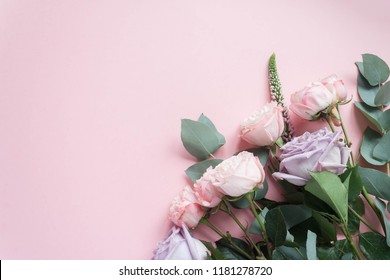 Frame of purple and pink roses, white Lisianthus and different flowers on pink background.
