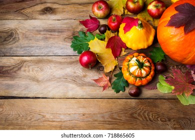 Frame of red apples, pumpkins and yellow gourd with colorful fall leaves, copy space. Thanksgiving or fall greeting background