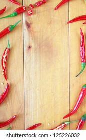 Frame of red chili peppers -- whole and cut -- on a wooden board.