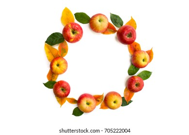 Frame of ripe yellow-red juicy apples and leaves on a white background with space for text. Top view, flat lay.