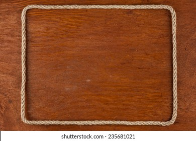 Frame of rope, lies on a background of a wooden surface, with place for your text