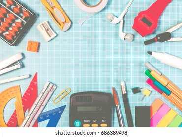 Frame of school education supplies on blue plastic cutting board mats with copy space for education background. Top view of school education background back to school concept.