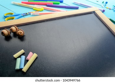 The frame of school supplies (pencils, paints, paper, brushes, markers) on a blackboard.