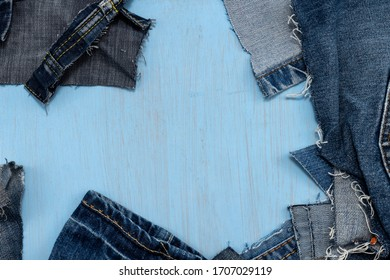Frame of scraps of old blue jeans on a painted blue wooden background. Top view with room for copy.