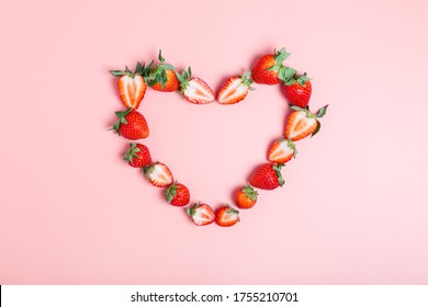 Frame in the shape of a heart made from ripe strawberries on a pink background. Beautiful background for the designer. Love concept. Valentine's day concept. border, flat lay, copy space.