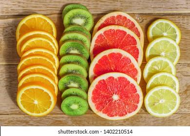frame with slice of oranges, lemons, kiwi, grapefruit pattern  on wooden background. copy space.