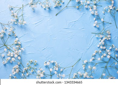 Frame  from tender  white gypsofila  flowers on blue textured background. Top view. Flat lay. Place for text.