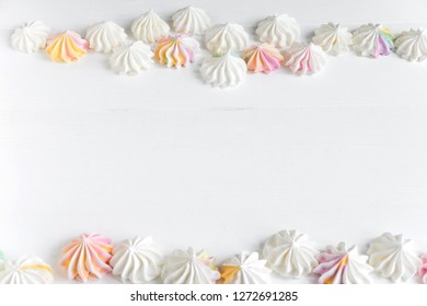 Frame for text with color meringues. Background for a banner with sweets. Multicolored meringues on a white wooden background. Basis for confectionery banner, cafe, sweet shop. Meringue banner