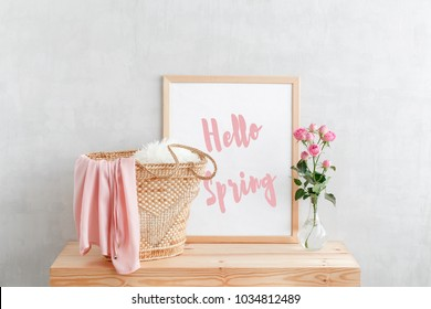 Frame with text HELLO SPRING, woven straw bag and vase with pink rose flowers on a wooden table on a background of light gray walls. Home interior decor.