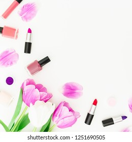 Frame with tulips flowers and cosmetics - lipstick and nail polish on white background. Top view. Flat lay feminine desk.