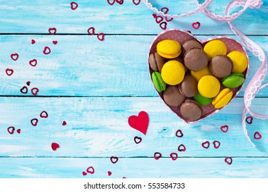 Frame Valentine's Day or a birthday, Mother's Day. Gifts makarons cake with heart on a blue wooden background. Top view with copy space.
