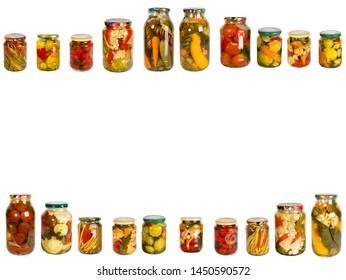 Frame from a variety of glass jars with canned vegetables on a white background. Homemade vegetables preserves.