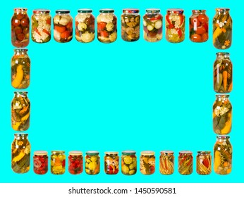 Frame from a variety of glass jars with canned vegetables on a blue background. Homemade vegetables preserves.