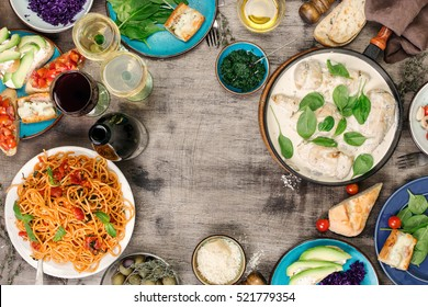 Frame from a variety of Italian dishes and snacks with red and white wine on wooden table, top view with copy space