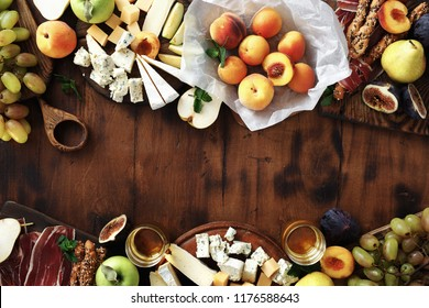 Frame of various wine snacks: grapes, peach, apricot, pear, apples, jamon, hard cheese, brie cheese and roquefort cheese on wooden table top view. Flat lay appetizers table for wine.