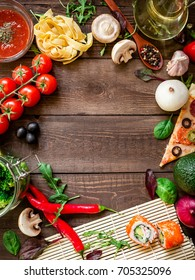 Frame with vegetables, pizza, sushi rolls, tomato, pasta, olives and sauce on wooden background. Food concept for menu. Flat lay. Top view.