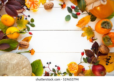 Frame from vivid colorful autumn leaves, natural seasonal background on white wooden background, top view.