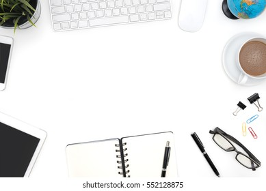 Frame of white office desk table background with computer, supplies, notebook, pen, pencil, tablet, phone, flower, globe, eye glasses and coffee cup, Top view with copy space
