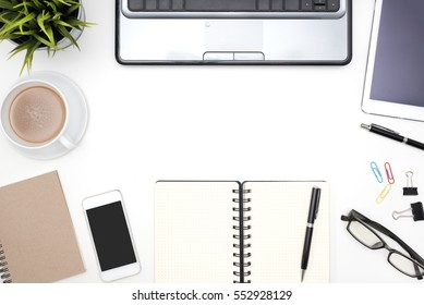 Frame of white office desk table background with computer, supplies, notebook, pen, pencil, tablet, phone, flower, eye glasses and coffee cup, Top view with copy space