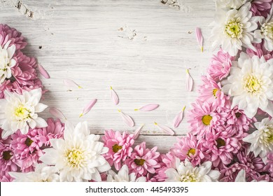 Frame of  white and pink flower on the white wooden table top view