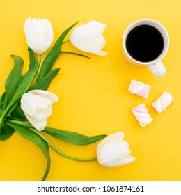 Frame of white tulips flowers with mug of coffee and marshmallows on yellow background. Floral concept. Flat lay, top view.