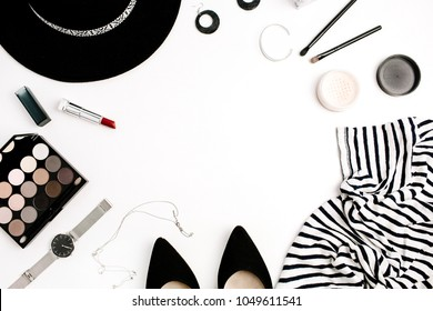 Frame of woman fashion modern clothes, accessories and cosmetics. T-shirt, hat, shoes, palette, lipstick, watches, powder on white background. Flat lay, top view.