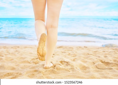 In the frame of a woman's feet walking on the beach by the sea on a Sunny day in a tropical hotel on vacation