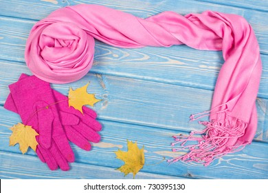 Frame of woolen gloves and shawl for woman on old boards, warm clothing for autumn or winter, copy space for text