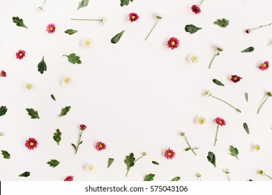 Frame wreath with red and white wildflowers, green leaves, branches on white background. Flat lay, top view. Flower background.