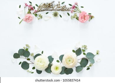 Frame wreath with white ranunculus flowers on white background. Flat lay, top view.