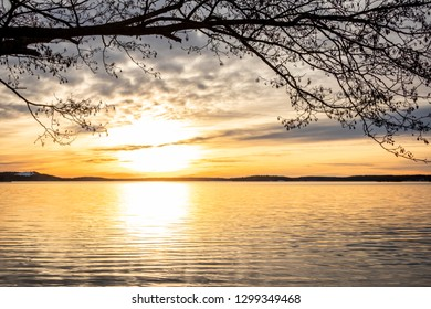 Framed beautiful orange winter landscape sunset over calm lake water with bright sun against sea horizon.