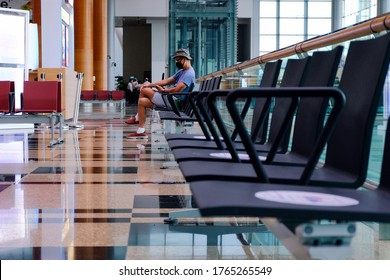 Framed composition shot of Asian man in airport, one person sitting alone at end of row of chairs, looking at his phone. Airport is empty. Selective focus.
