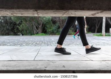 Framed picture of a trendy woman's legs wearing cropped black pants and black shoes walking on a pedestrian area