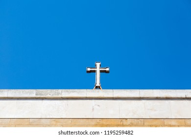 A framed stone cross on top of a church in Bari, Italy