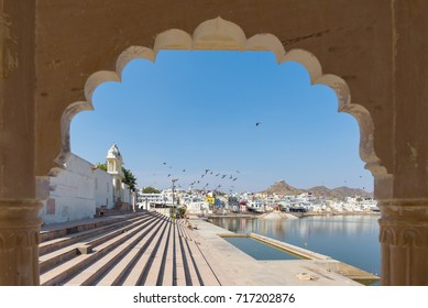 Framed view from archway at Pushkar, Rajasthan, India. Temples, buildings and ghats on the holy water of the lake.