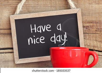 Framed vintage blackboard with a red cup of steamy coffee against wooden background with copy space with Have a nice day message