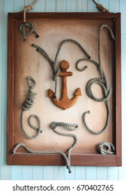 Framed wooden anchor and knots as decoration on wall