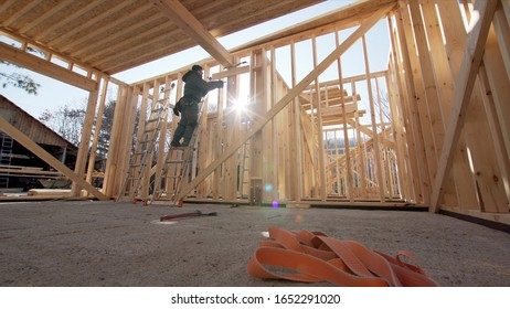 Framer attaching beams with hydraylic hammer at frame house building