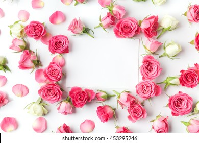 Framework from roses on white background. Flat lay.