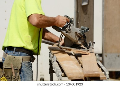 Framing contractor worker cutting spacer block for trim using a small circular saw on a new commercial residential development