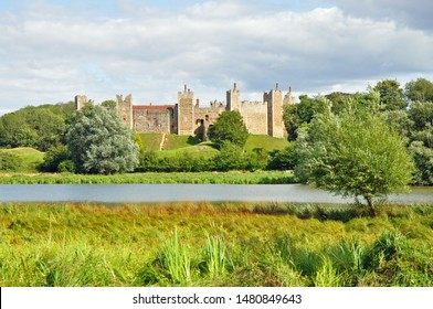 Framlingham, Suffolk, United Kingdom, August 15, 2019. Medieval Castle on hill shot across the Mere (lake) with tree in right foreground. Framlingham, Suffolk, United Kingdom, August 15, 2019