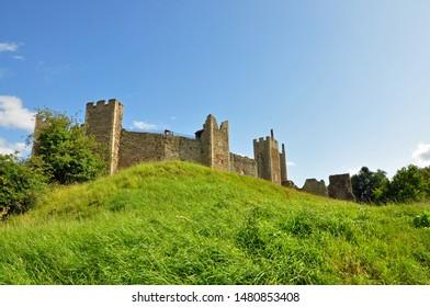 Framlingham, Suffolk, United Kingdom, August 15, 2019. Medieval Castle walls shot from below, at bottom of steep bank on public footpath. Framlingham, Suffolk, United Kingdom, August 19, 2019.