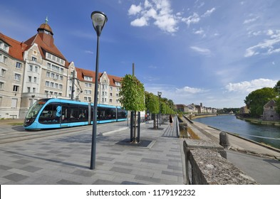 Besançon, France - August 17, 2018: The Cité Universitaire building, the tramway on the Quai Veil Picard, the Doubs River and the Pont Battant in the background.