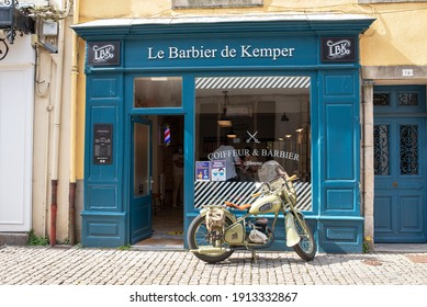 """France, Bretagne - July 2020: Barber shop in Bretagne, France with old motorcycle in the front and text """"Le Barbier de Kemper"""" on blue facade"""