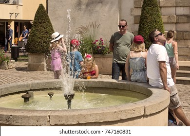 France, Burgundy, Beaune: Citizens residents tourists children young old relax at water fountain in the city center of the famous French small town - concept vacation people travel. August 03, 2017