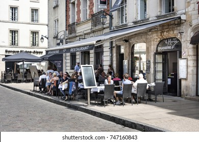 France, Burgundy, Beaune: Typical street scene with people in front of a restaurant. The town is one of the key French wine centers and of Burgundy wine production and business. August 03, 2017